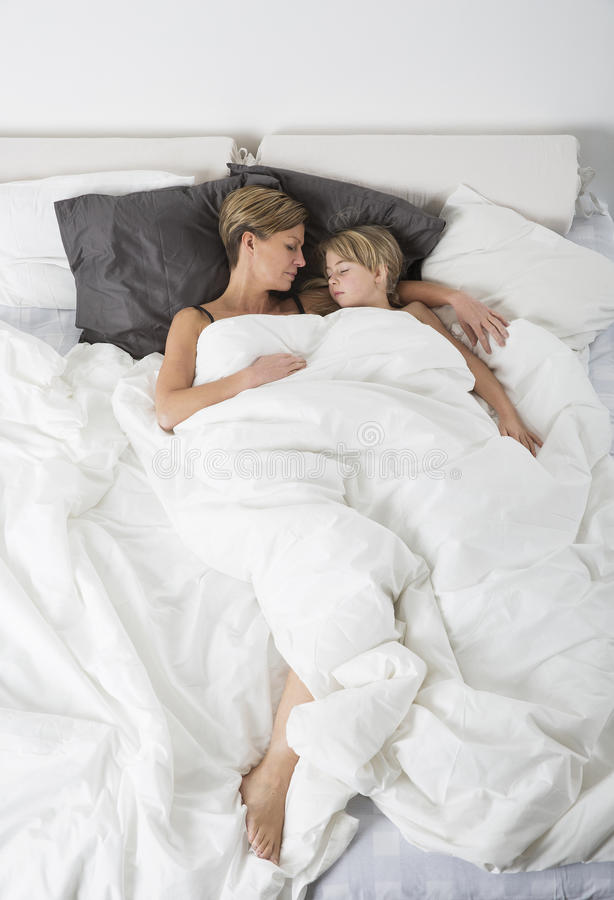 Mother and daughter sleeping from high angle view stock photo