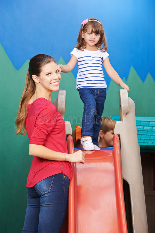 Mother and daughter on slide stock photos