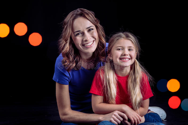 Mother and daughter smiling at camera royalty free stock images