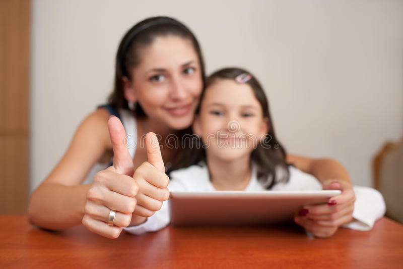 Mother and daughter smiling and showing thumb stock images