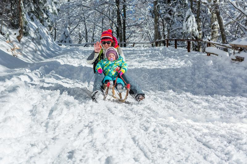 Mother and daughter speeding downhill on wooden sledge. royalty free stock photo