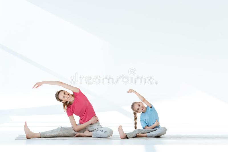 Mother and daughter in sportswear exercising on yoga mats stock photos