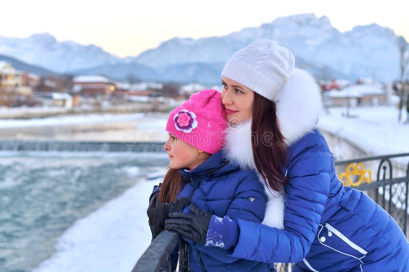 A mother and daughter standing arm in arm on the seafront mountain river in winter stock photos