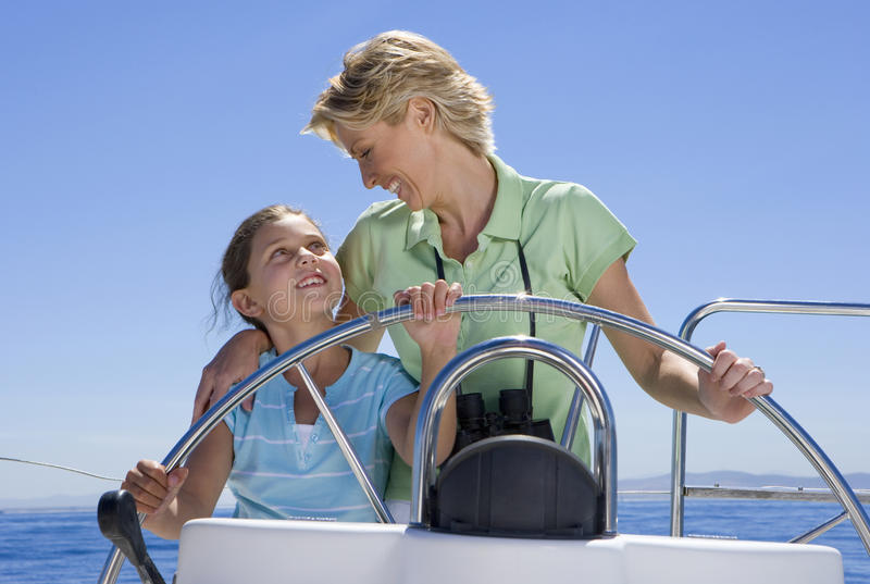 Mother and daughter (8-10) standing at helm of sailing boat out at sea, steering, smiling at one another, front view stock image