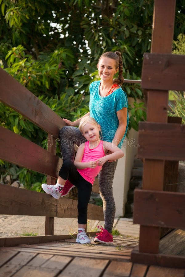 Mother and daughter standing on wood bridge at beach. A young blonde daughter and her mother are standing together on a wooden bridge, smiling and happy. They royalty free stock photo