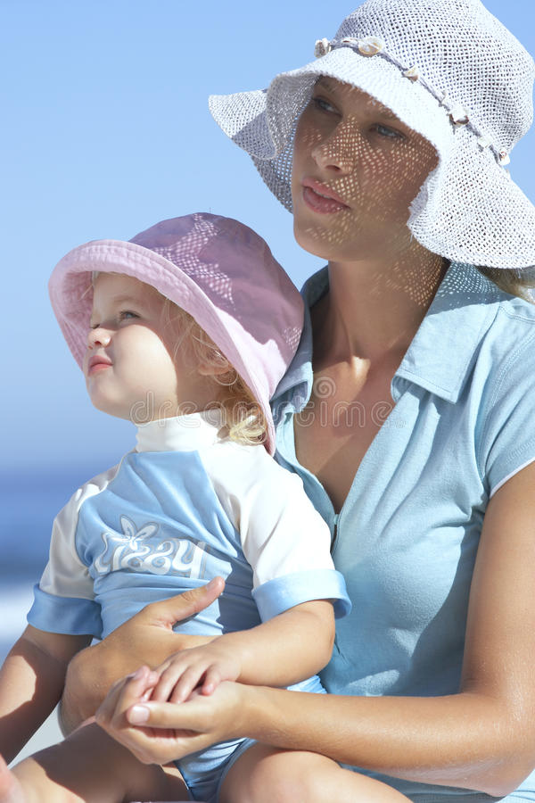 Mother and daughter (2-4) in sun hats sitting on beach, girl in woman's lap, close-up royalty free stock photo