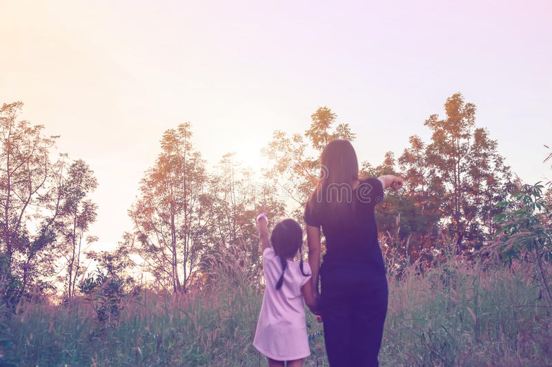 Mother and daughter on sunset watching on sky royalty free stock photography