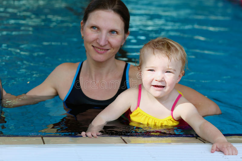 Mother and daughter swimming in the pool. Happy little child, adorable toddler girl, having fun in the swimming pool together with her young mother stock photography