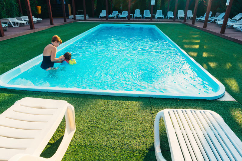 Mother And Daughter Jumping Into Swimming Pool Stock