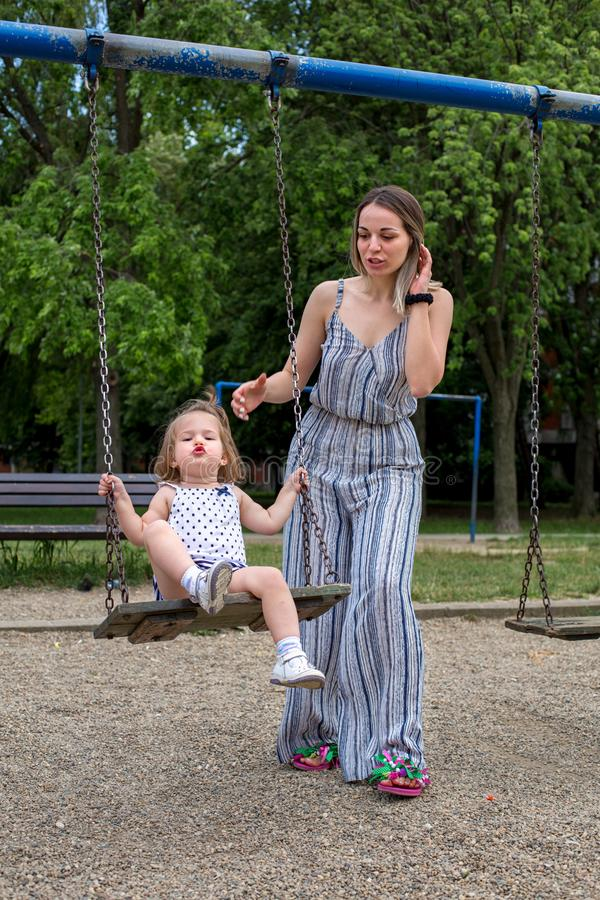 Mother with daughter on swing royalty free stock photo