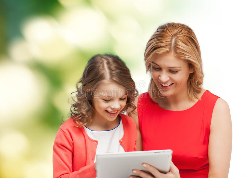 Mother and daughter with tablet pc computer. Family, child and technology concept - smiling mother and daughter with tablet pc computer stock photos