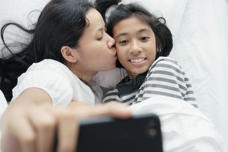 Mother and daughter are taking a picture together. Asian women and cute girl so fun and happy  selfie on the bed stock images