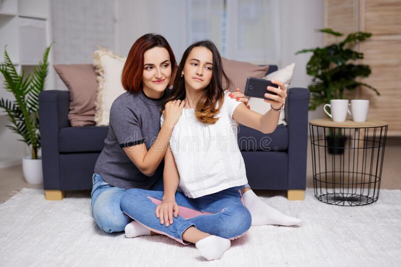 Mother and daughter taking selfie photo with smartphone. In living room royalty free stock photography