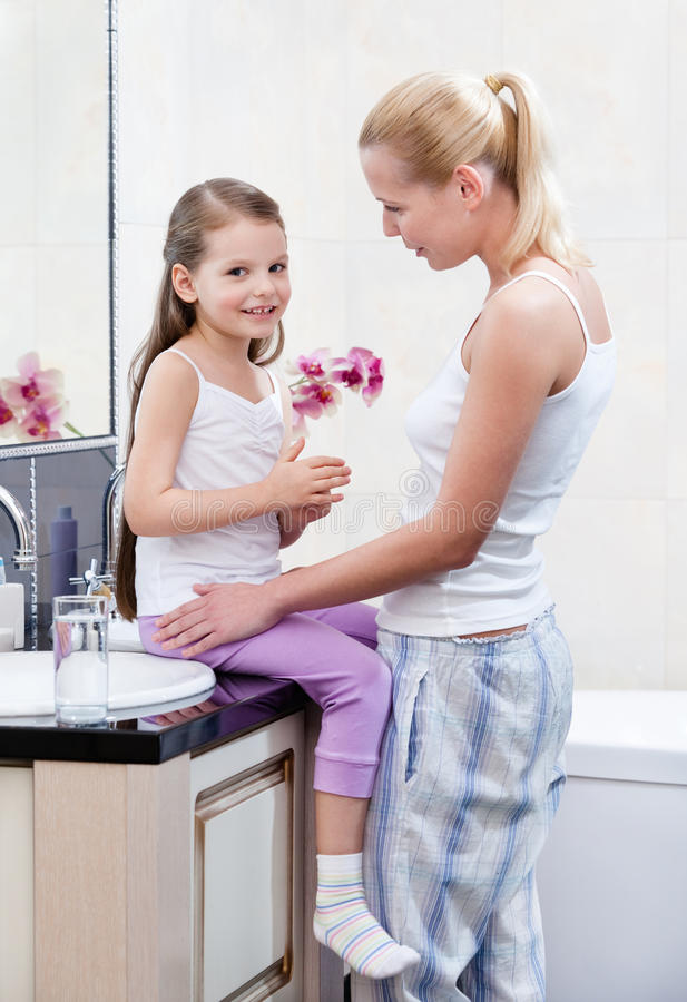 Mother and daughter talk in bathroom