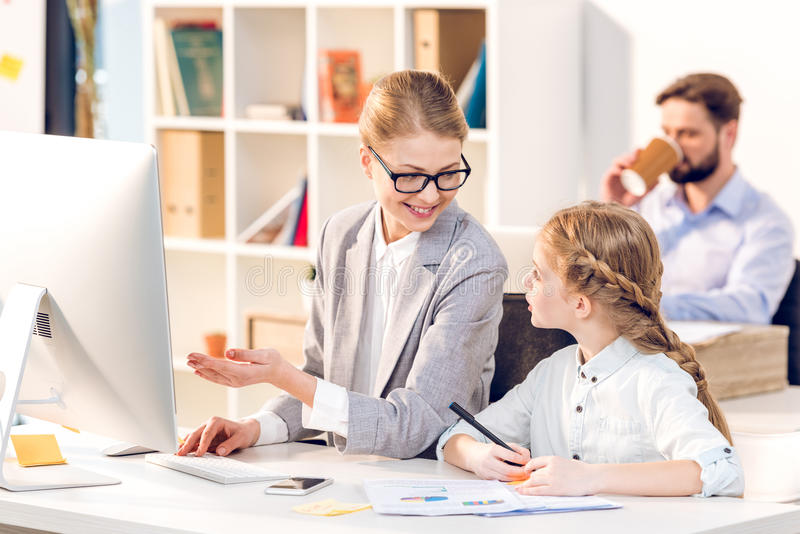 Mother and daughter talking in business office, father behind royalty free stock image