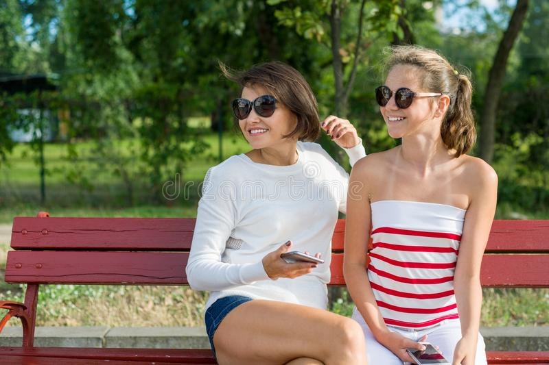 Mother and daughter teenager looking to the side, sitting on a bench in the park. Communication between parent and child. stock photography