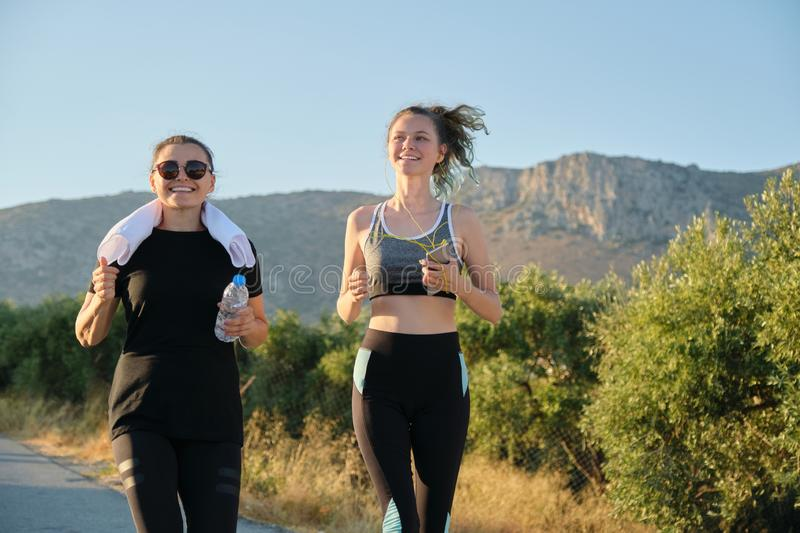 Mother and daughter teenager running outdoor on road in mountains royalty free stock photography