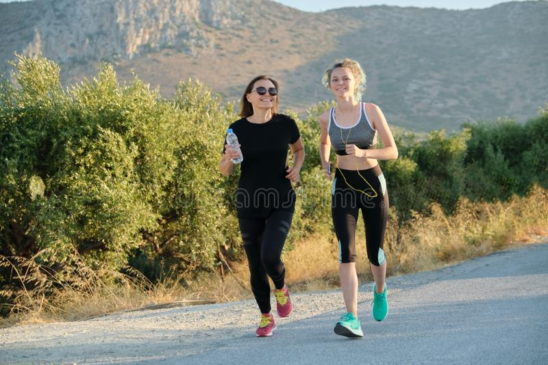 Mother and daughter teenager running outdoor on road in mountains royalty free stock photo