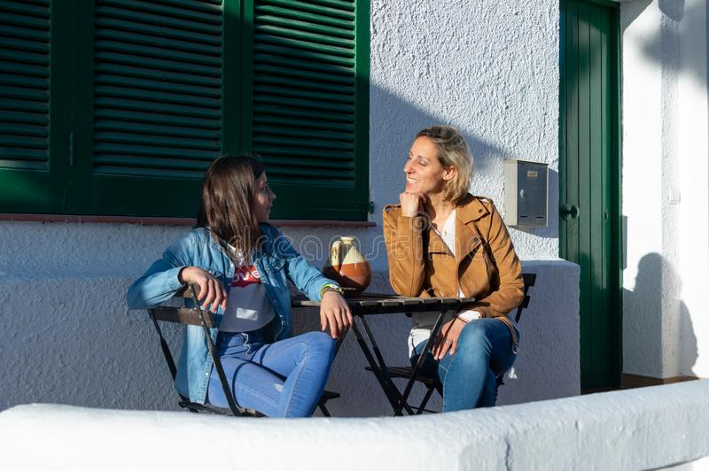 Mother and daughter teenager sitting on green furniture terrace in typical european coastal town of Barcelona, in Spain royalty free stock image