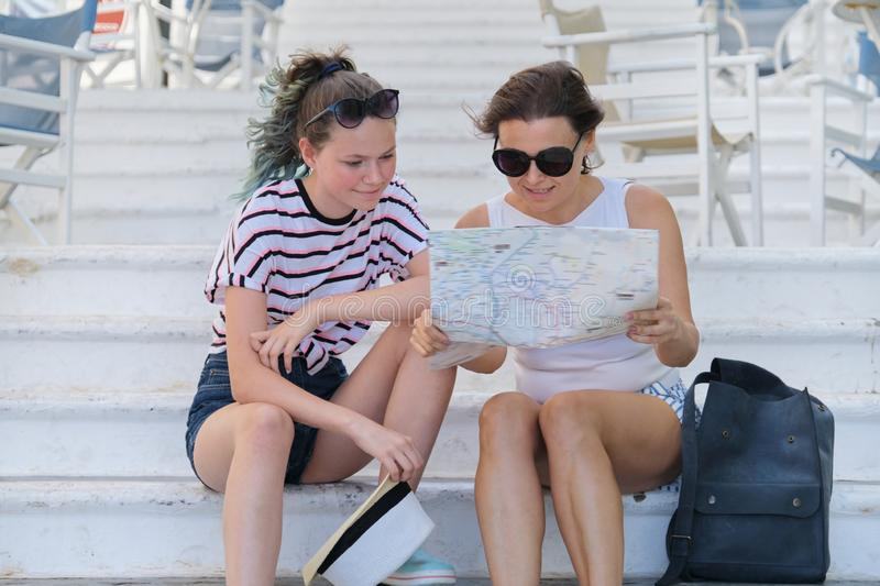 Mother and daughter teenager traveling together, women reading tourist map royalty free stock photography