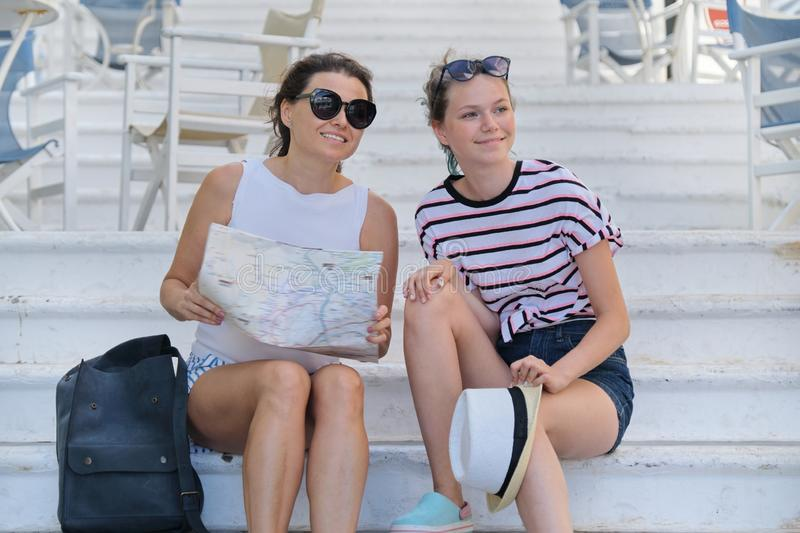 Mother and daughter teenager traveling together, women reading tourist map stock image