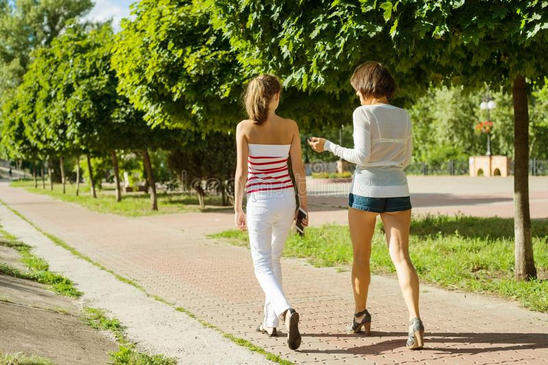 Mother and daughter teenager walking through the city park on a summer sunny day. stock photos