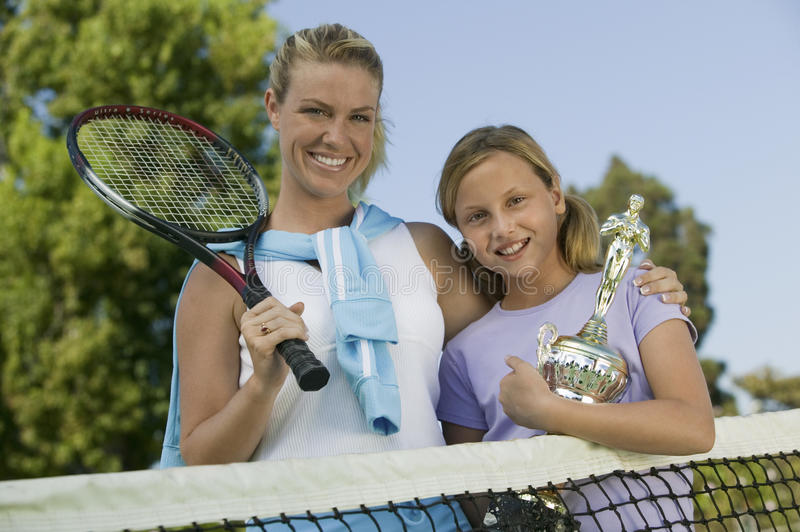 Mother and Daughter at Tennis Net with Trophy portrait low angle view stock photos