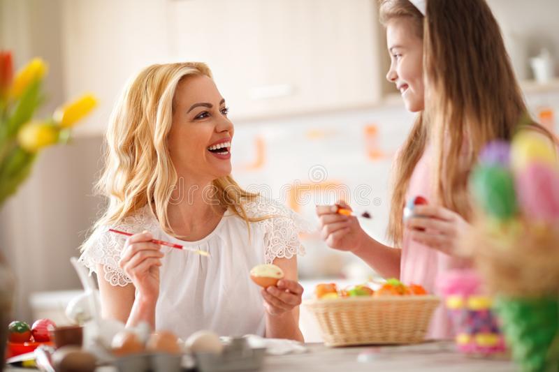 Mother and daughter together coloring Easter eggs royalty free stock images