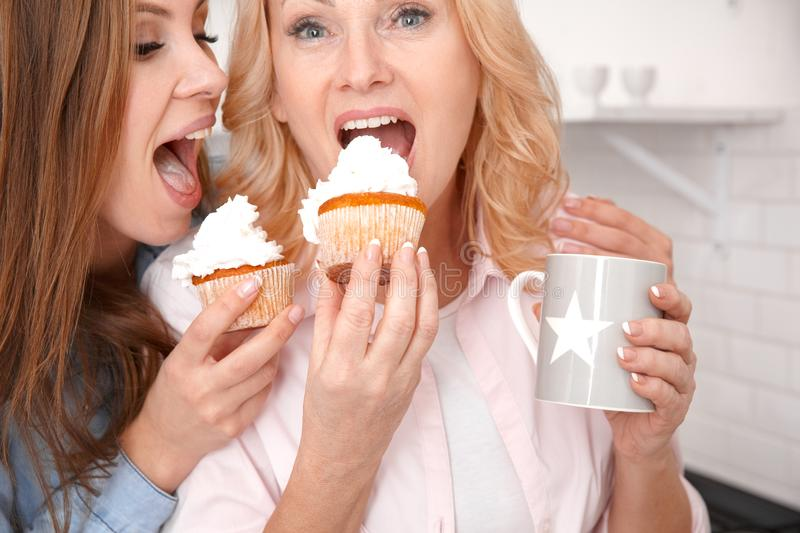 Mother and daughter together at home weekend close-up eating cakes. Middle-aged mother and young daughter together at home weekend close-up drinking coffee stock photography