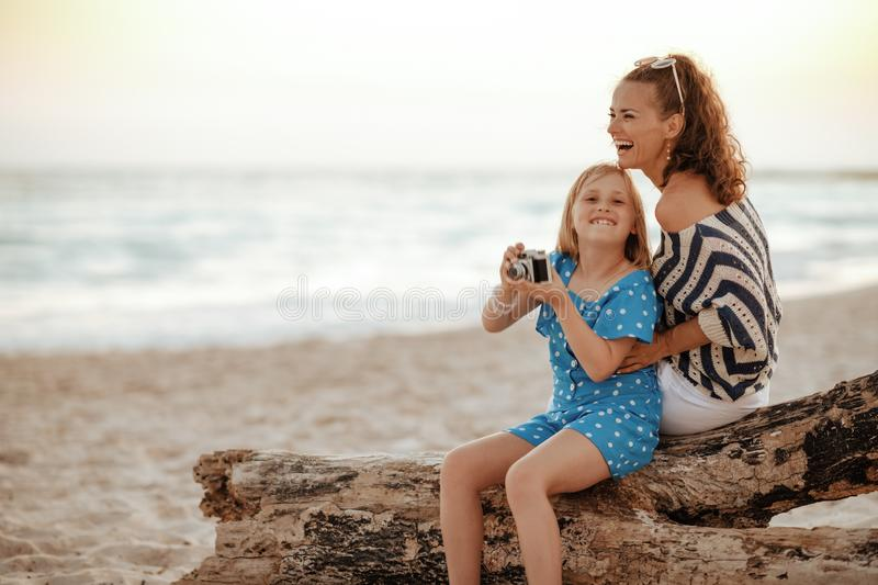 Mother and daughter tourists sitting on a wooden log stock image