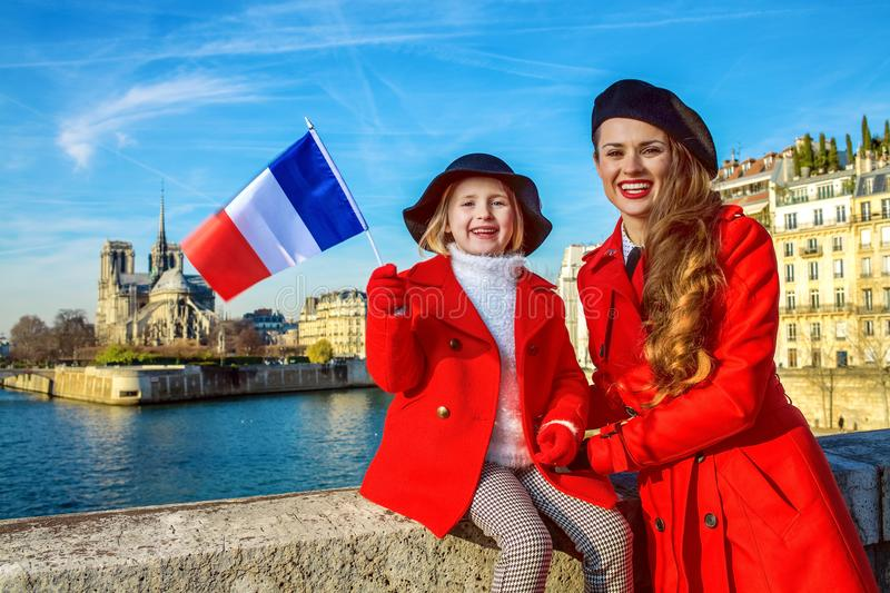 Mother and daughter travellers in Paris, France showing flag. Bright in Paris. modern mother and daughter travellers in red coats on embankment in Paris, France stock images