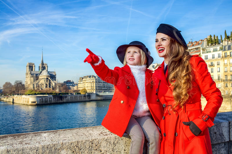 Mother and daughter travellers in Paris pointing at something. Bright in Paris. modern mother and daughter travellers in red coats on embankment near Notre Dame stock photos