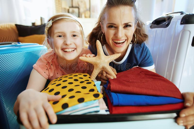 Mother and daughter travellers preparing for summer trip. Happy trendy mother and daughter travellers in the modern house in sunny summer day showing starfish stock images