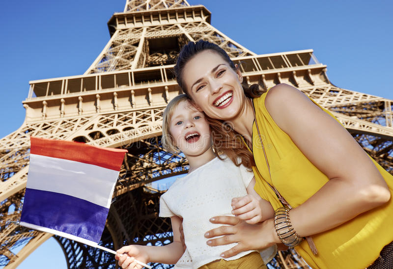 Mother and daughter travellers showing flag near Eiffel tower. Touristy, without doubt, but yet so fun. happy mother and daughter travellers showing flag against royalty free stock photography