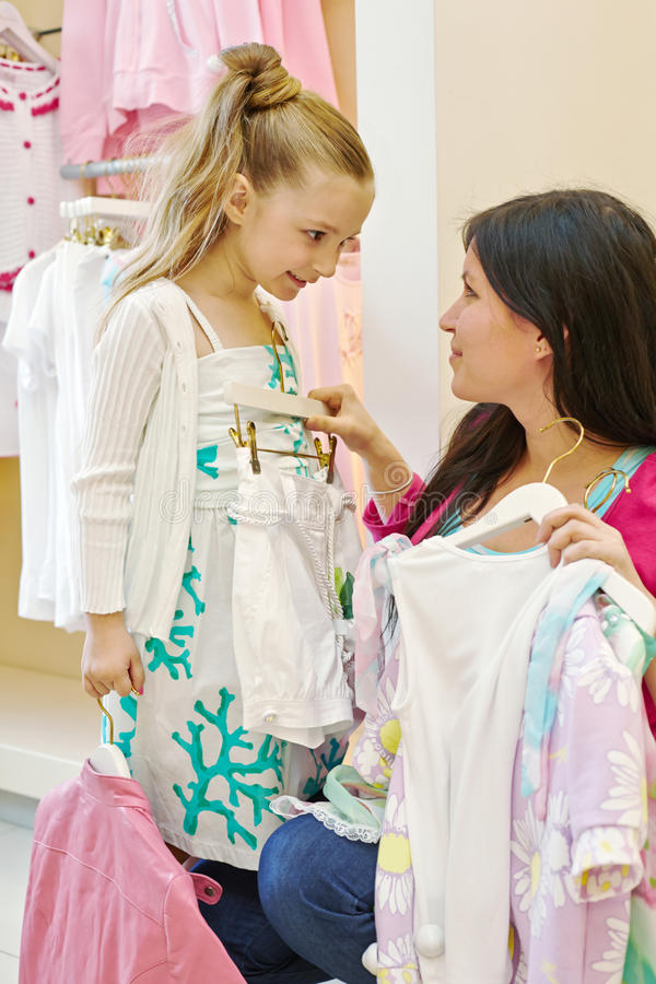 Mother and daughter try on clothes. In clothing store stock photos