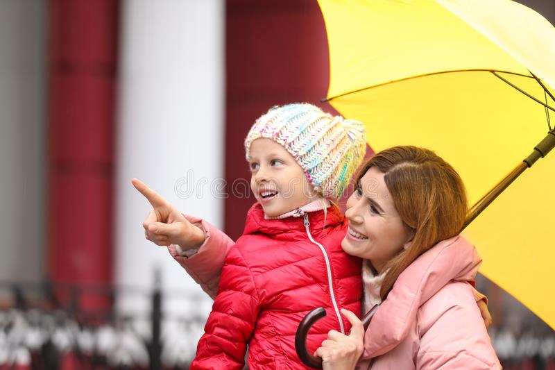 Mother and daughter with umbrella in city stock images