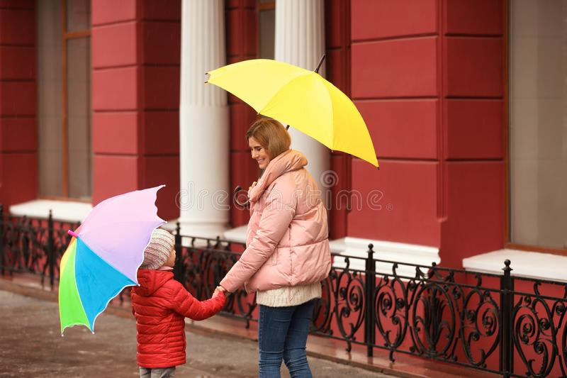 Mother and daughter with umbrellas in city stock photos