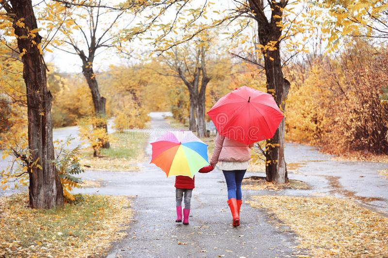 Mother and daughter with umbrellas taking walk in autumn park royalty free stock image