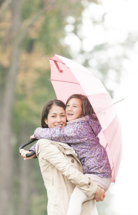 Mother and daughter under umbrella in autumn. stock images