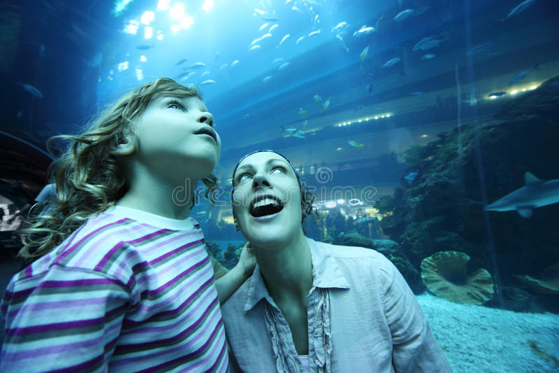 Mother and daughter in underwater aquarium tunnel royalty free stock photo