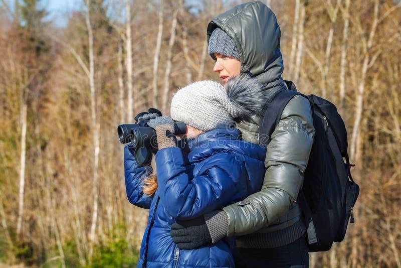 Mother and daughter using binoculars stock photo