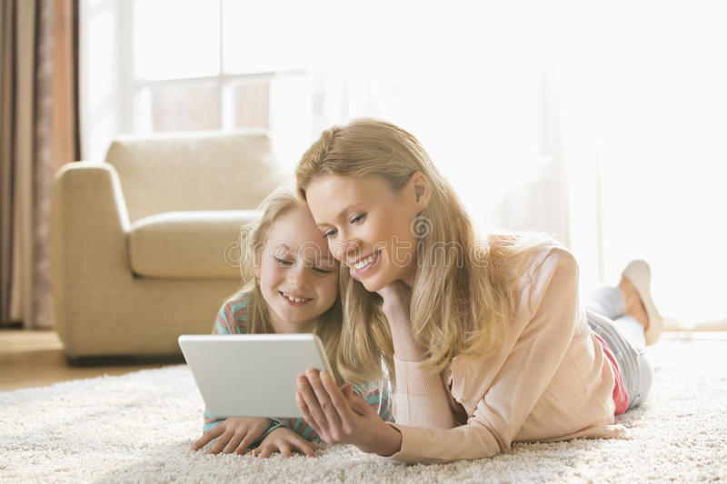 Mother and daughter using digital tablet on floor at home royalty free stock images