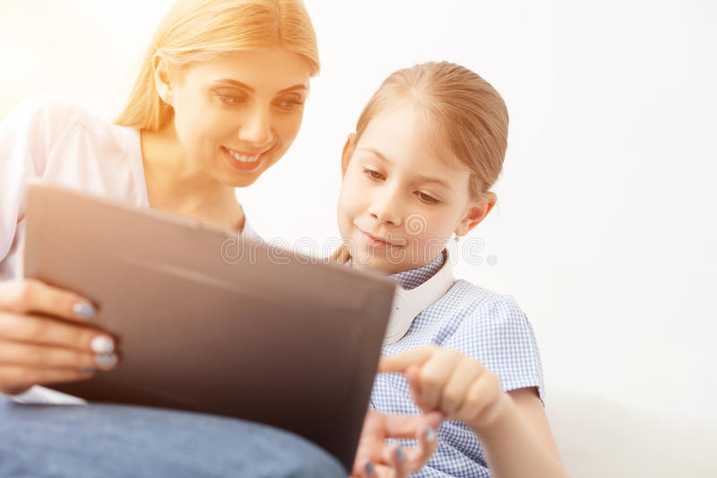 Mother and daughter using digital tablet. Showing her how to surf. Shot of mother using digital laptop with her little daughter stock photography