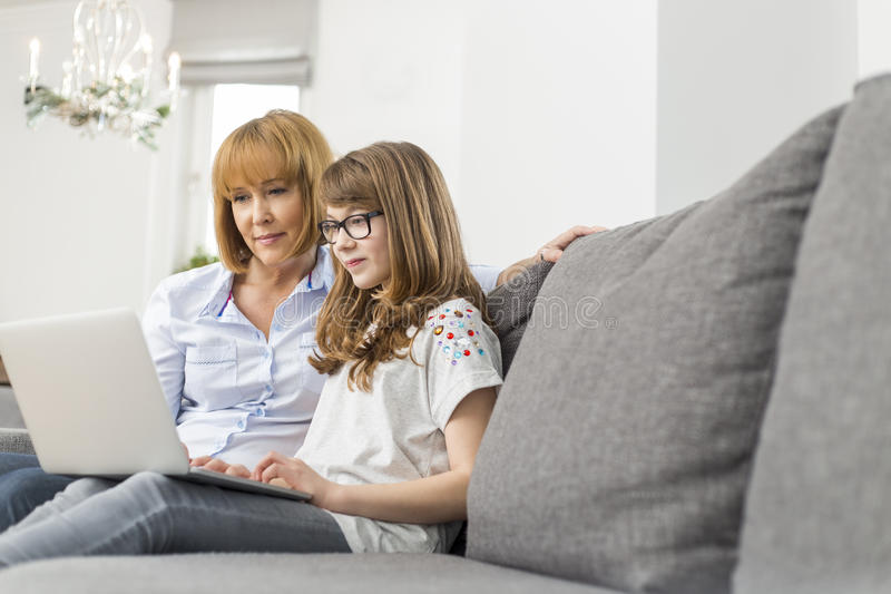 Mother and daughter using laptop together at home stock photo