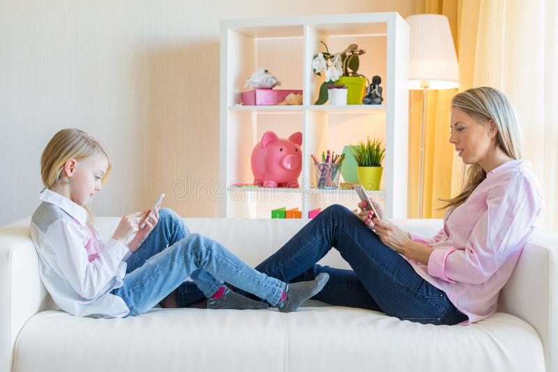 Mother and daughter using phones while sitting on sofa. Smartphone  addiction concept royalty free stock photo