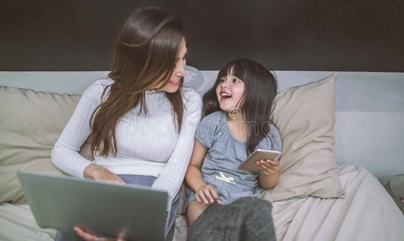 Mother and daughter using smartphone and laptop together in bedroom. technology concept. royalty free stock photography