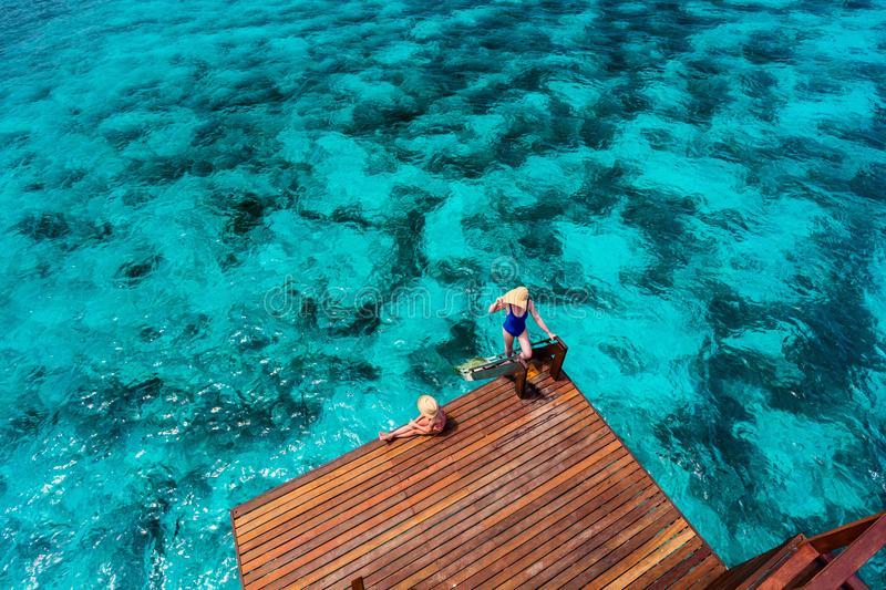Mother and daughter on vacation. Mother and daughter at wooden dock of overwater villa in Maldives stock photo