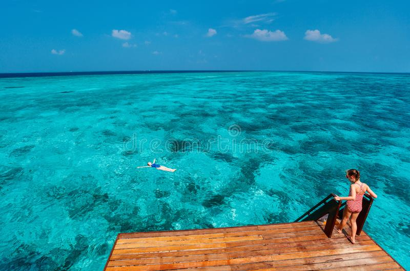 Mother and daughter on vacation. Mother and daughter at wooden dock of overwater villa in Maldives royalty free stock image