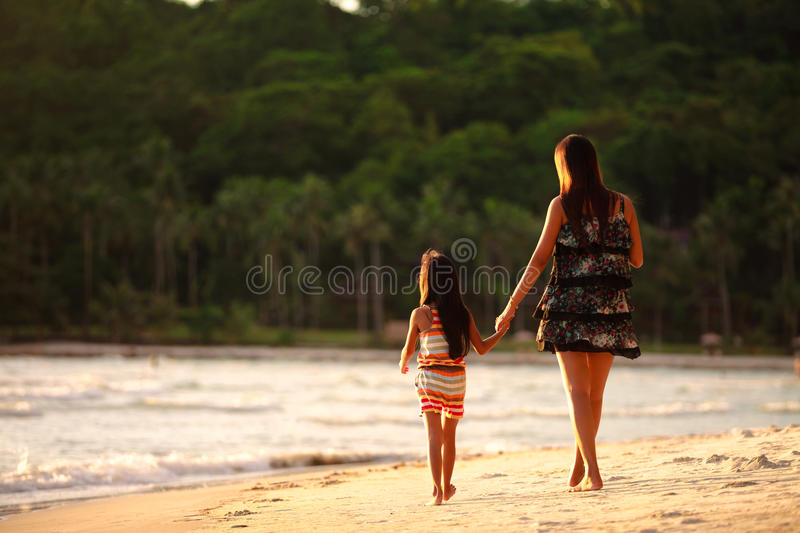Download Mother And Daughter Walking On Beach Stock Photo - Image of edge, concept: 31895330