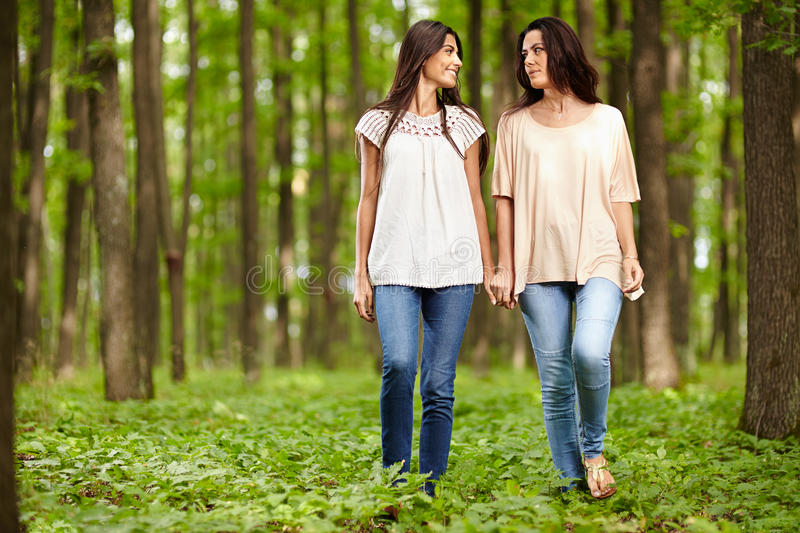 Mother and daughter walking hand in hand stock photo